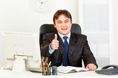 Smiling businessman showing thumbs up gesture Stock Photo