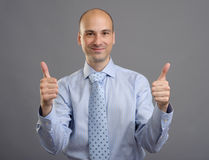 Smiling businessman showing thumbs up sign Stock Image