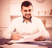 Smiling businessman is signing agreement papers. Of financial nature at home Stock Photos