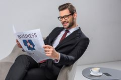 smiling businessman sitting in armchair stock photo