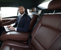 Smiling businessman sitting in the back seat of a prestigious ca Stock Photography