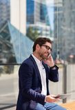 Smiling businessman sitting on a bench using a tablet and cellphone. Smiling young businessman sitting on a bench in the city talking on his cellphone and using Royalty Free Stock Photos
