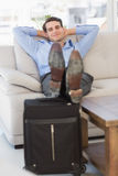Smiling businessman sitting on couch with feet up on suitcase Stock Photo