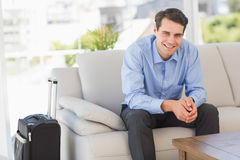 Smiling businessman sitting on couch waiting to leave on business trip Stock Photos