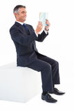 Smiling businessman sitting on a cube reading a book Stock Images