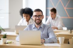 Smiling businessman sitting at desk with laptop in office, portr. Smiling businessman in glasses sitting at desk with laptop in shared office, attractive Stock Photo