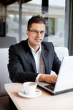 Smiling businessman sitting at desk with laptop Stock Photo