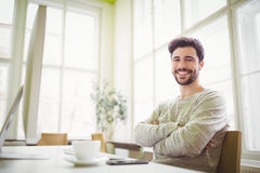 Smiling businessman sitting at desk in office Stock Image