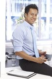Smiling businessman sitting on desk in office Stock Photography