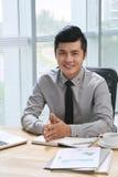 Smiling businessman sitting at desk Stock Photo
