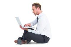 Smiling businessman sitting on floor using laptop Royalty Free Stock Photo