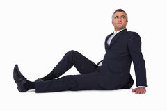Smiling businessman sitting on the floor stock photography