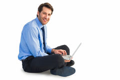 Smiling businessman sitting on floor working on laptop Royalty Free Stock Photos