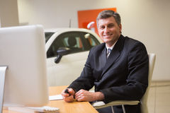 Smiling businessman sitting at his desk holding a car key Stock Photos