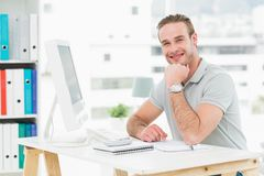 Smiling businessman sitting at his desk Royalty Free Stock Image