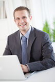 Smiling Businessman Sitting at His Laptop Stock Images