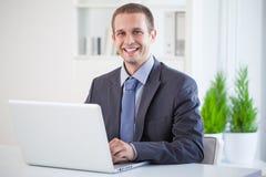 Smiling Businessman Sitting at His Laptop stock image