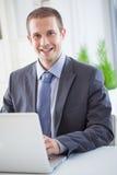 Smiling Businessman Sitting at His Laptop royalty free stock image