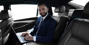 Free Smiling Businessman Sitting In The Back Seat Of A Prestigious Car Royalty Free Stock Photo - 112410055