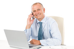 Smiling businessman sitting in office behind desk Stock Photos