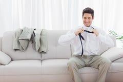 Smiling businessman sitting on sofa loosening his tie Royalty Free Stock Image