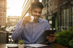 Businessman sitting in street cafe drinking coffee and u. Smiling businessman sitting in street cafe drinking coffee and using iPod Royalty Free Stock Photography