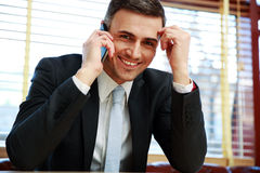 Smiling businessman sitting stock images