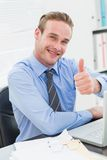 Smiling businessman sitting with thumb up Stock Photos