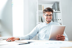 Smiling businessman sitting and using tablet computer in office Royalty Free Stock Photos