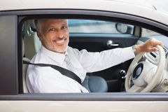Smiling businessman sitting at the wheel of a car for sale Royalty Free Stock Photo