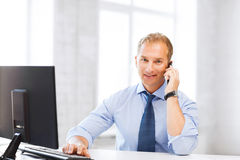 Smiling businessman with smartphone in office Royalty Free Stock Images
