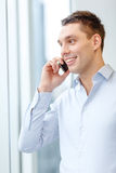 Smiling businessman with smartphone in office Stock Photography