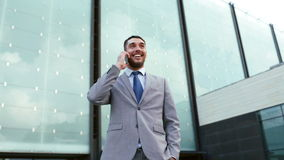 Smiling businessman with smartphone outdoors Stock Photo