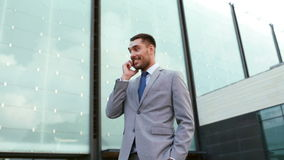 Smiling businessman with smartphone outdoors Royalty Free Stock Photos