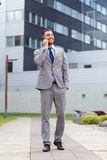Smiling businessman with smartphone outdoors Stock Photos