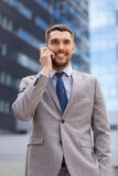 Smiling businessman with smartphone outdoors Royalty Free Stock Image