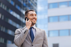 Smiling businessman with smartphone outdoors Royalty Free Stock Photo
