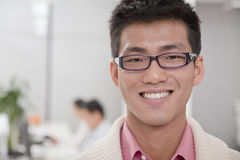 Smiling Businessman smiling in the office, coworkers in the background Stock Image