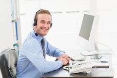 Smiling businessman speaking with headset. In his office Royalty Free Stock Images