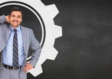 Smiling businessman standing against cog wheel on black background Stock Photo