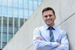 Smiling businessman standing against wall Stock Photo