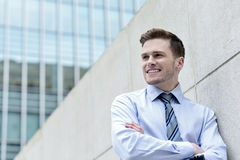Smiling businessman standing against wall Royalty Free Stock Photos