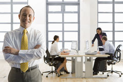Smiling businessman standing with arms crossed and co-workers working in background Stock Photos