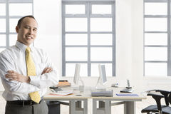 Smiling businessman standing with arms crossed in office Royalty Free Stock Images
