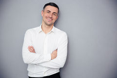 Smiling businessman standing with arms folded Stock Photos