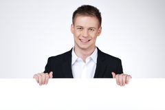 Smiling businessman standing behind the blank poster. Royalty Free Stock Photo