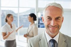Smiling businessman standing in front of colleagues Royalty Free Stock Images