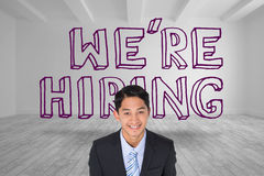 Smiling businessman standing in front of were hiring graphic. In grey room Stock Image