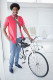 Smiling businessman standing with his bike Stock Photography