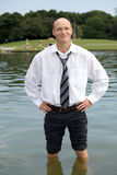 Smiling businessman standing in lake with hands on hip Royalty Free Stock Images